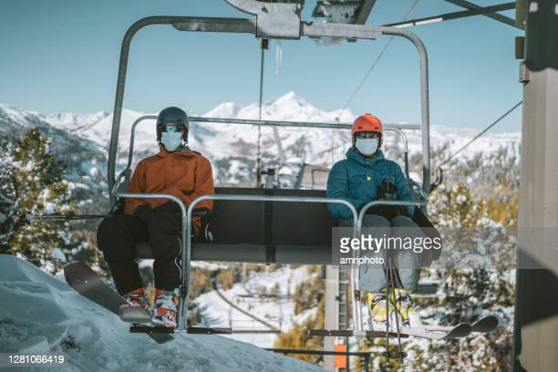 two skiers with mouth nose mask on chair lift - coronavirus winter stock pictures, royalty-free photos & images