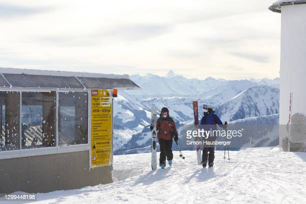 Two skiers with protective face masks get off a ski lift station at the top of the hohe salve mountain at the Austrian Ski Resort Skiwelt on January...