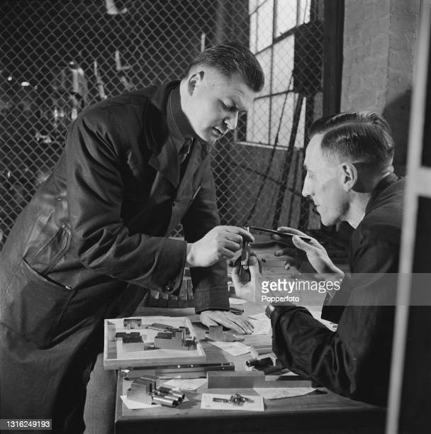Two skilled Czechoslovak technicians inspect Bren Gun parts turned out at a munitions factory in England during World War II on 7th April 1941. The...