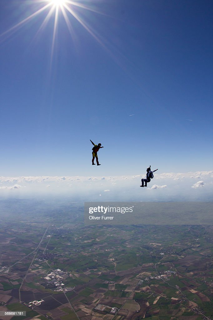 Two skydivers are flying together in the blue sky : Stock Photo