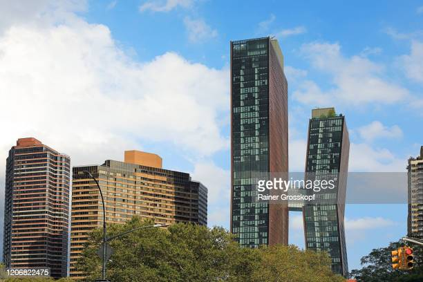 two skyscrapers connected by a sky bridge in the middle of the building height - rainer grosskopf stock pictures, royalty-free photos & images
