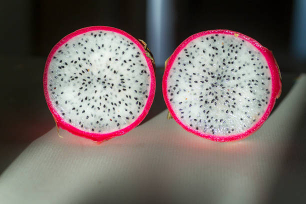 Two slices of dragon fruit laying on white foreground and dark background
