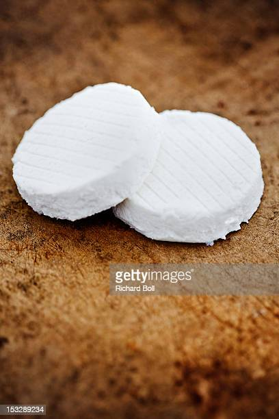 Two slices of goat cheese on a wooden board