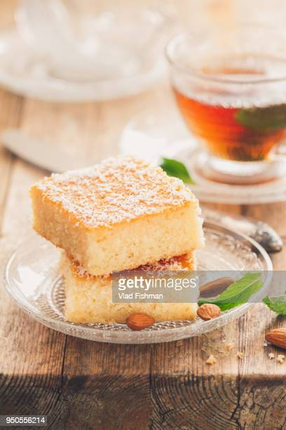 two slices of homemade semolina cake on a wood vintage rustic table background with mint tea - couscous stock pictures, royalty-free photos & images