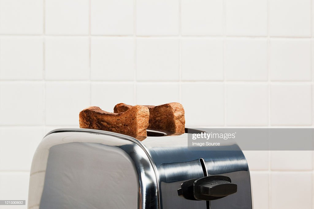 Two slices of toast in toaster : Stock Photo