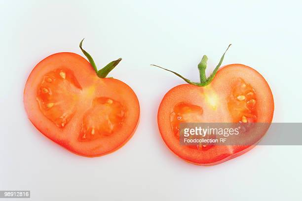 Two slices of tomato with calyxes, elevated view, close-up