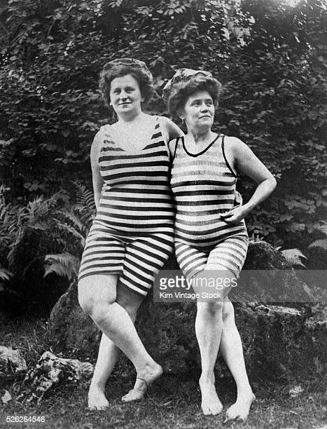 Two slightly plump women stand together wearing their swimming suits