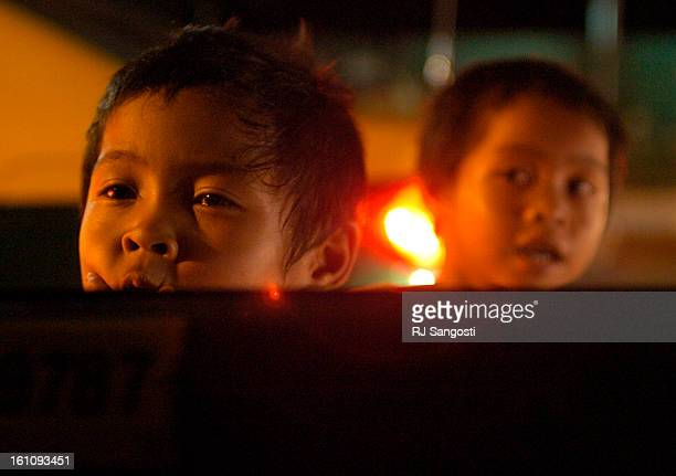 AUG 21 2006 Two small boy run to a taxi window in hope for a handout Monday Aug 21 in Bangkok Thailand Many children in the area living on the...