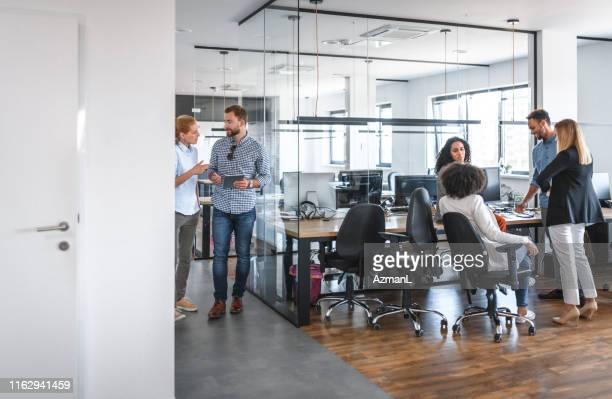 zwei small business group diskussionen im open plan office - großraumbüro stock-fotos und bilder