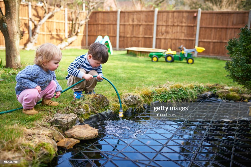 Two small children filling up a pond with a hoes : Stock Photo
