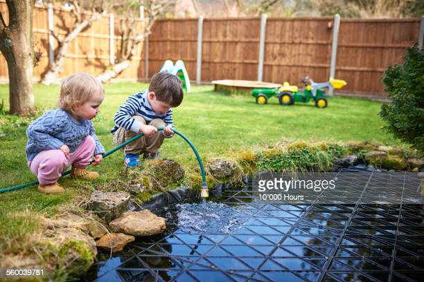 Two small children filling up a pond with a hoes