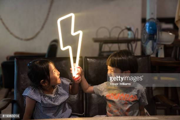 Two small children holding a lightning bolt shaped neon light