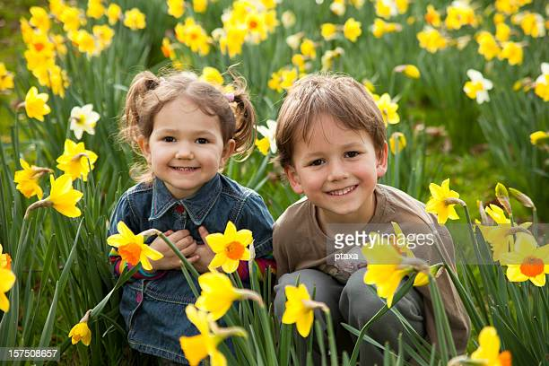 Two small children smiling in a field of daffodils