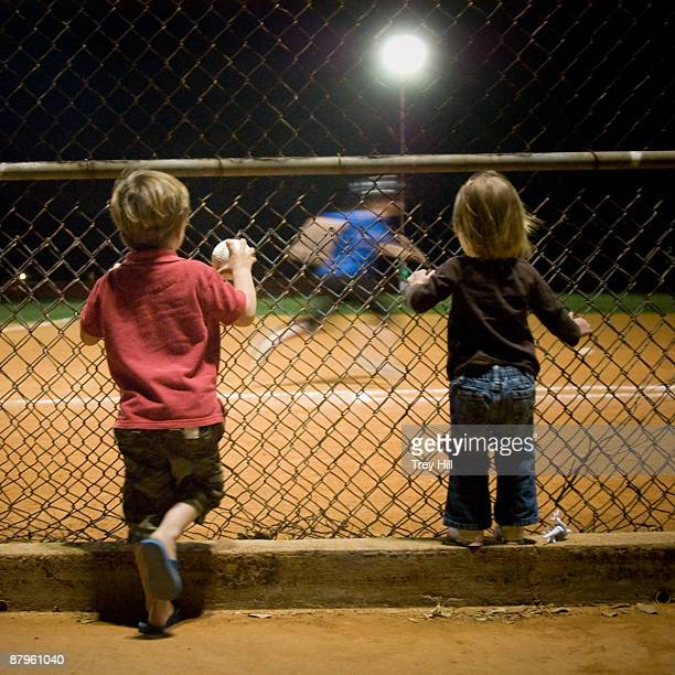 Two small children watch a night baseball game.