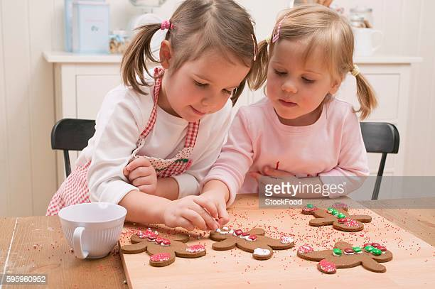 two small girls decorating gingerbread men - accompagnement photos et images de collection