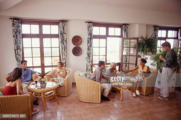 Two Small Groups Sitting At Coffee Tables In Cafe High Res Stock