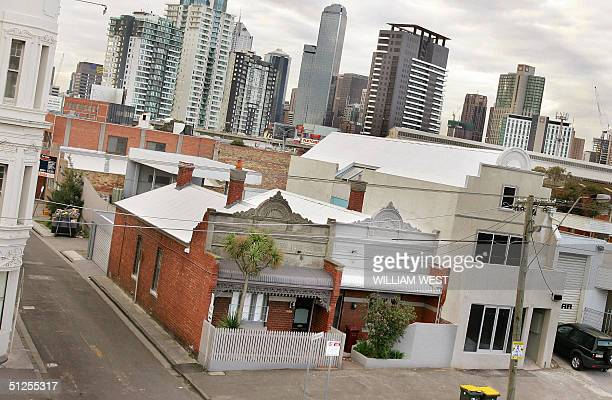 Two small houses in the innercity suburb of South Melbourne are dwarfed by the city skyline as a record quarterly fall in house prices confirmed...