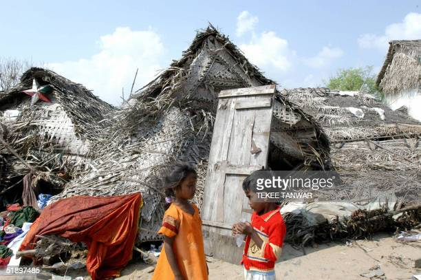 Two small Indian children share a plastic container of water in front of destroyed buildings at an emergency camp in the grounds of Santhome Church...
