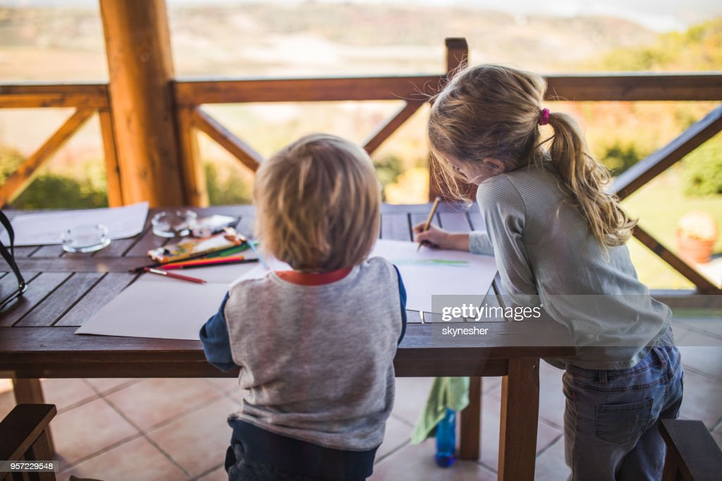 Two small kids having fun while drawing on a balcony. : Stock Photo