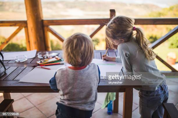 two small kids having fun while drawing on a balcony. - colouring stock photos and pictures