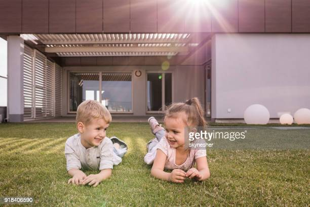 two small kids talking while relaxing on grass in front of their house. - penthouse girls stock pictures, royalty-free photos & images