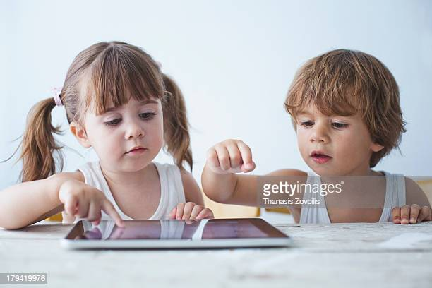 two small kids using a tablet - nur kinder stock-fotos und bilder