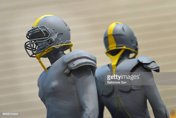 Two small models show how the safety straps might look on the helmet in Aberdeen Md on December 8 2015 The US Army Research Laboratory at Aberdeen...