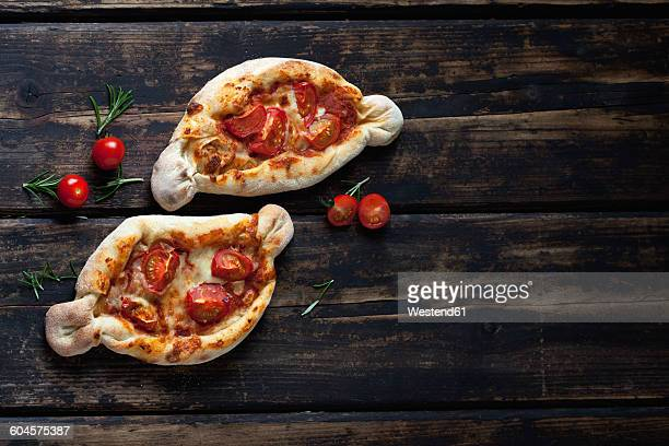 Two small pizzas, rosemary and cherry tomatoes on dark wood
