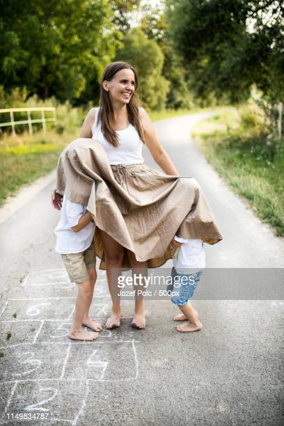 two small sons playing with mother on a road in park on a summer day - under the skirt stock photos and pictures