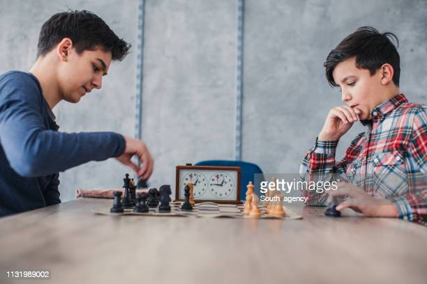 two smart boys playing chess in school of chess - south_agency stock pictures, royalty-free photos & images