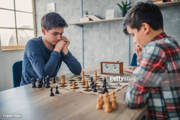 two smart boys playing chess in school of chess - chess stock pictures, royalty-free photos & images