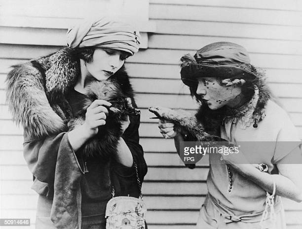 Two smartlydressed women stage a mock fight with their mink stoles circa 1925