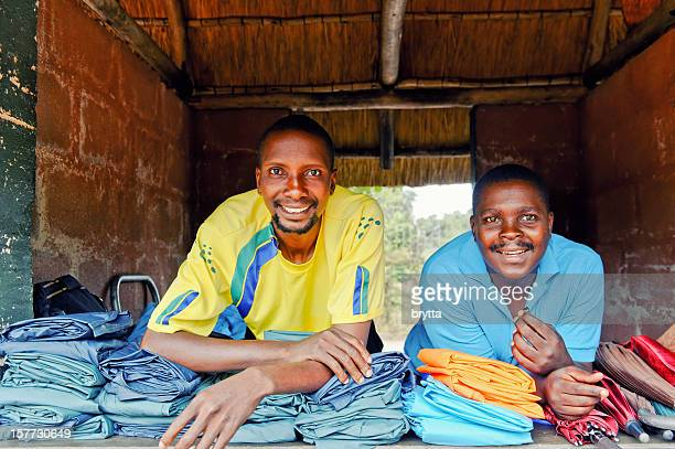 Two smiling African vendors renting rain clothing in shop,Zimbabwe