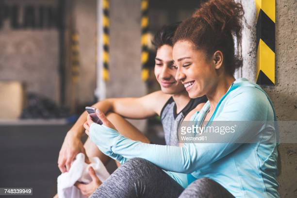 Two smiling athletes sharing cell phone in gym