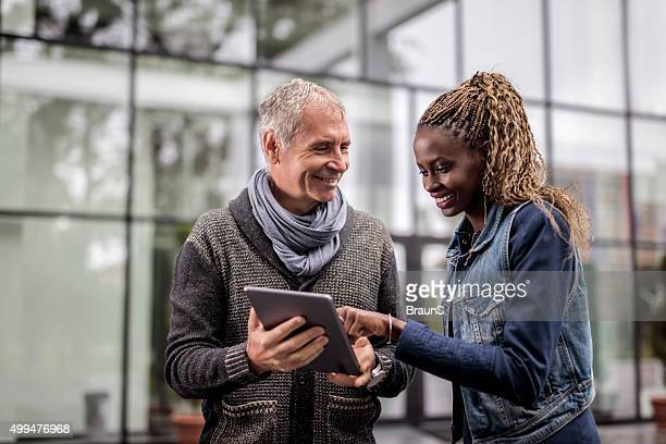 Dois colegas de negócios sorridente, trabalhando em tablet digital ao ar livre.