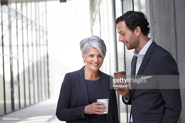 Two smiling business people with coffee to go