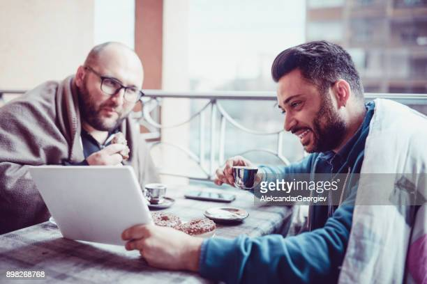 Two Smiling Businessman on Coffee Break Looking at Laptop