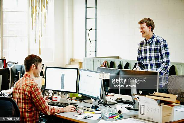 Two smiling businessmen in discussion in office