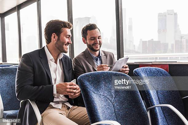 Two smiling businessmen with document talking on passenger deck of a ferry