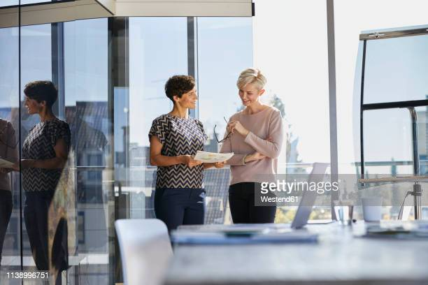 two smiling businesswomen discussing document at the window in office - german short haired pointer stock pictures, royalty-free photos & images