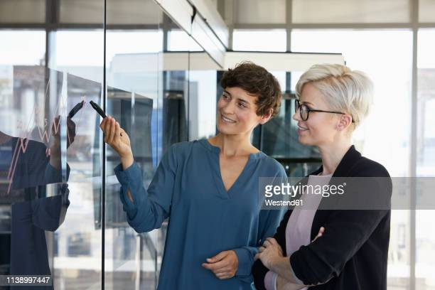 two smiling businesswomen looking at chart on glass pane in office - german short haired pointer stock pictures, royalty-free photos & images