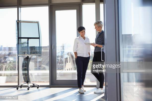two smiling businesswomen looking at tablet at the window in bright office - german short haired pointer stock pictures, royalty-free photos & images