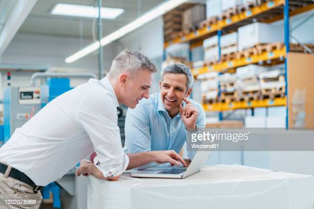two smiling colleagues using laptop and discussing in a factory - concepts & topics stock pictures, royalty-free photos & images