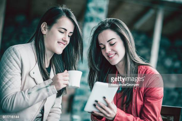 two smiling cute friends make video conference with digital tablet and drink coffee outdoors - coffee drink stock pictures, royalty-free photos & images