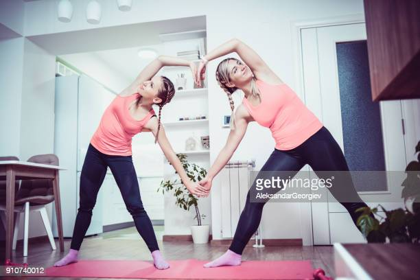 Two Smiling Cute Girls Making Heart with Hands and Supporting Fitness and Healthy Life