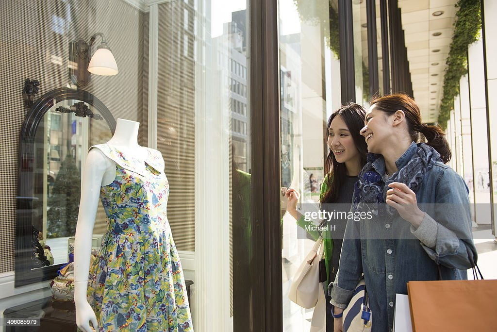 Two smiling female friends window shopping : Stock Photo