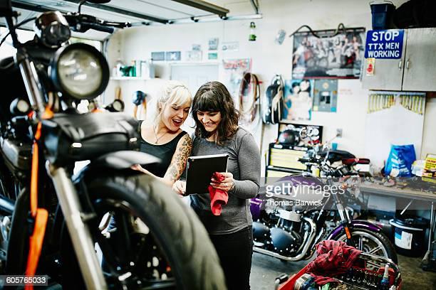Two smiling female mechanics working on motorcycle