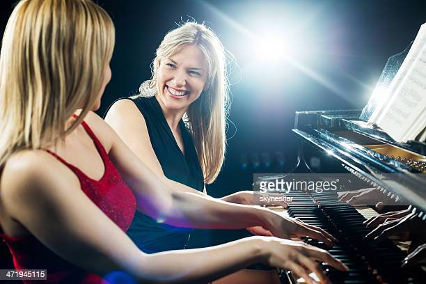 Two smiling female pianists.