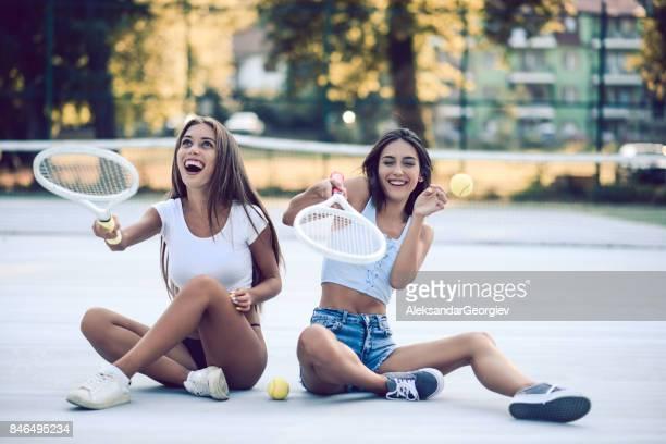 deux femelles souriantes posant sur un court de tennis et jongler avec la raquette et la balle - raquette de tennis photos et images de collection