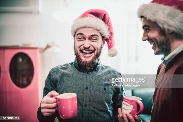 twee lachende vrienden drink cacao en hebben een grappig gesprek - funny christmas stockfoto's en -beelden